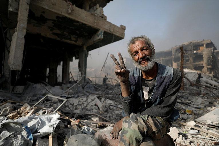 Мужчина на развалинах поврежденных зданий в Аль-Хаджар Аль-Асвад, Сирия