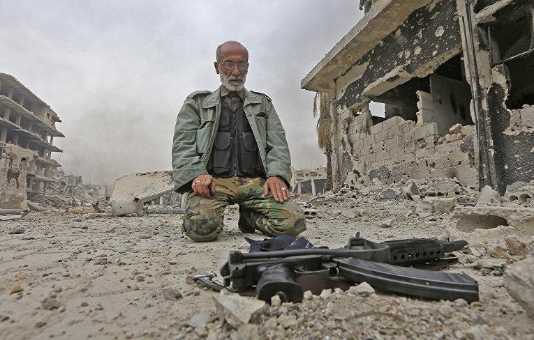 Военнослужащий на разрушенной улице в районе Хаджар Аль-Асвад на окраине столицы Дамаска