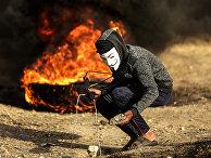 Палестинский демонстрант в маске Гая Фокса во время столкновений с израильскими силами правопорядка на границы с сектором Газа