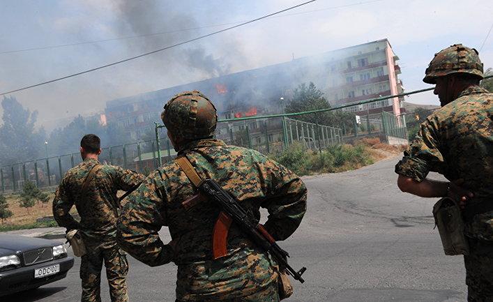 Грузинские солдаты наблюдают за горящим зданием, пострадавшим от обстрелов в Гори