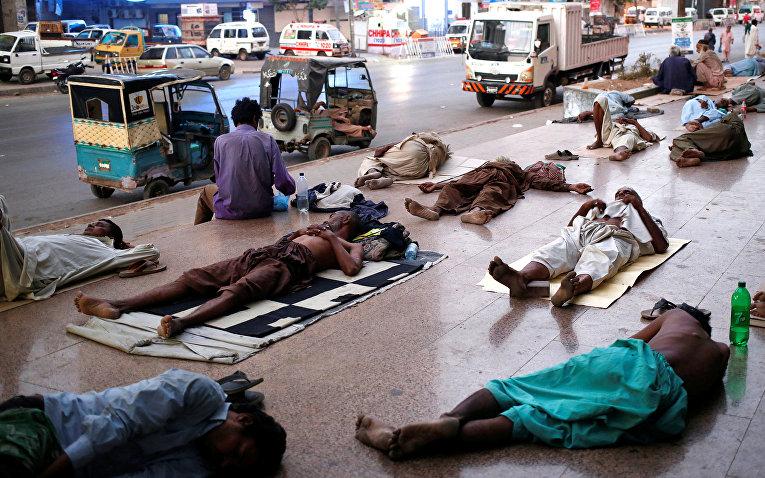 Местные жители спят на тратуарах спасайсь от жары и отключений электроэнергии в Карачи, Пакистан