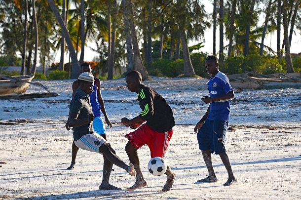 Местные жители играют в футбол на пляже в Занзибаре, Танзания