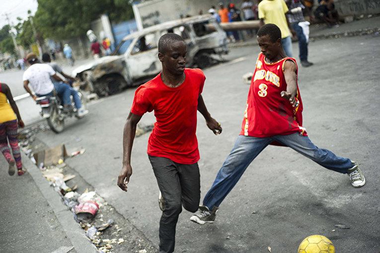Местные жители играют в футбол на улице в Порт-о-Пренсе, Гаити