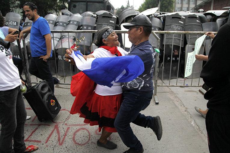 Пара танцует перед полицейской баррикадой во время протеста в Тегусигальпе, Гондурас