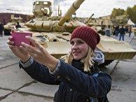 Посетитель фотографируется на фоне танка Т-90А на 10-й международной выставке Russia Arms Expo