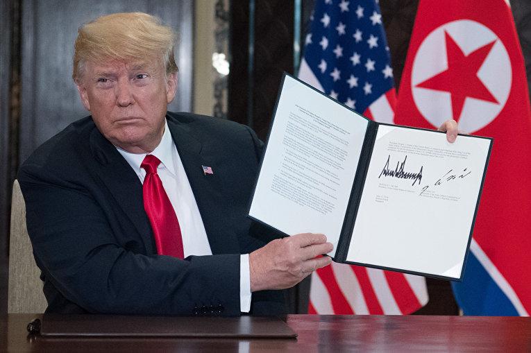 Президент США Дональд Трамп с подписанным совместно с лидером КНДР Ким Чен Ыном документом по итогам встречи в Сингапуре. 12 июня 2018