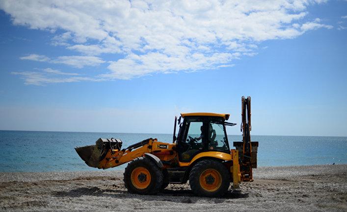 Трактор ровняет щебень на пляже в Ялте