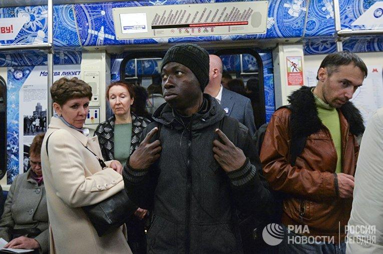 Пассажиры в поезде московского метрополитена, оформленного ко Дню космонавтики и посвященного 55-летию первого полета человека в космос