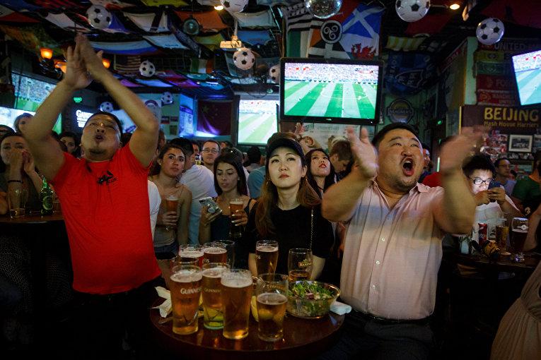 Люди смотрят футбольный матч чемпионата мира по футболу между командами России и Саудовской Аравии в баре в Пекине, Китай