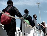 Африканские мигранты высаживаются из спасательного судна «Аквариус» после прибытия в порт в Валенсии
