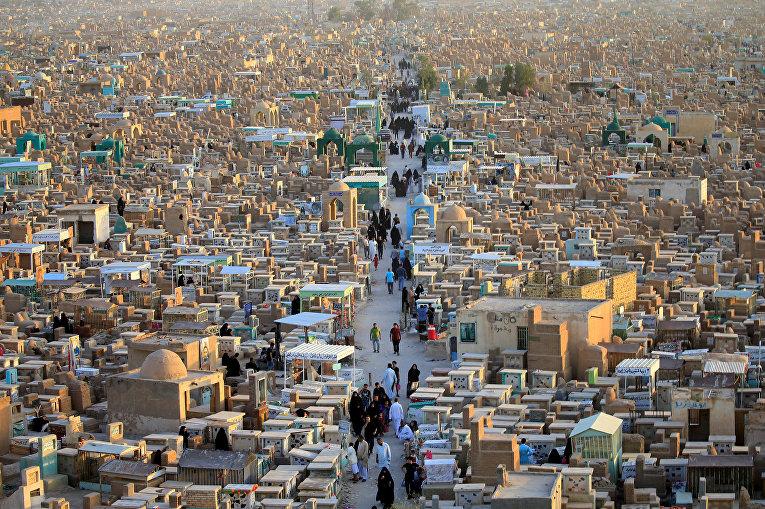 Люди посещают кладбище «Долина мира», отмечая конец месяца поста Рамадана