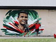 Болельщики рисуют граффити с изображением игрока сборной Португалии Криштиану Роналду перед матчем ЧМ-2018 по футболу между сборными Ирана и Португалии в Саранске.