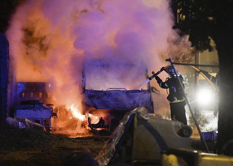 Пожарный во время тужения горящего автомобиля в Нанте, Франция