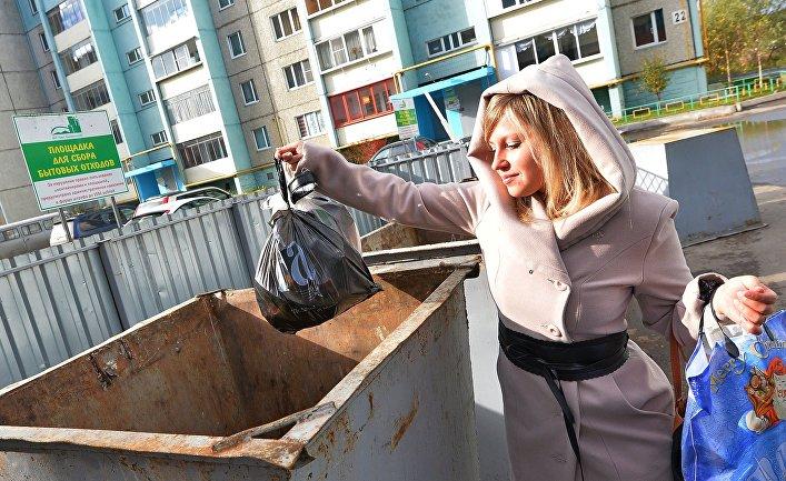 Девушка выбрасывает мусор в городе Миасс Челябинской области.