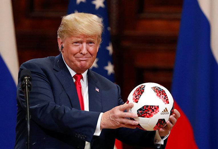 Президент США Дональд Трамп держит футбольный мяч, который ему дал президент России Владимир Путин