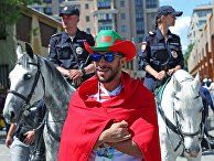 Болельщик сборной Марокко и конная полиция перед матчем Чемпионата мира по футболу между сборными Португалии и Марокко в Москве