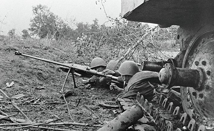 Гвардейцы-бронебойщики отражают танковую атаку врага, лежа рядом с подбитым танком. Курская дуга