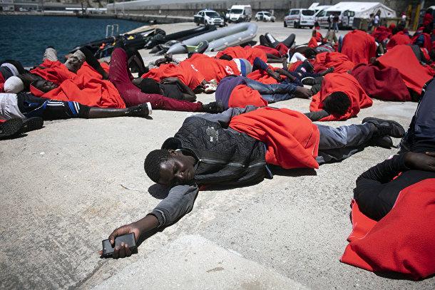 Мигранты, спасенные спасательной службой Испании отдыхают в порту города Тарифа в Испании