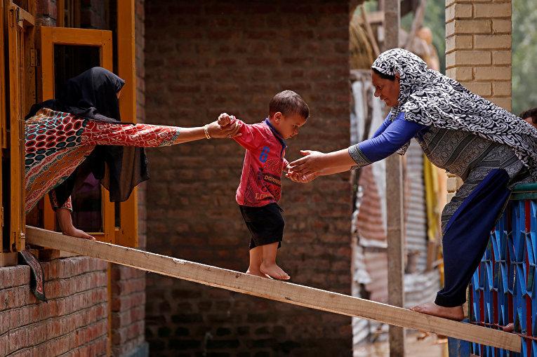 Женщины помогают ребенку перебраться в другой дом во время наводнения в индийском городе Сринагар