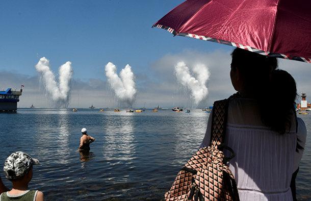 Люди смотрят парад ко Дню Военно-Морского Флота во Владивостоке
