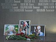 Цветы у фотографий погибших в Центральноафриканской Республике журналистов: Орхана Джемаля, Кирилла Радченко и Александра Расторгуева возле Дома журналистов в Москве. 1 августа 2018