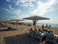 Отдыхающие на пляже на берегу Черного моря в поселке Оленевка на мысе Тарханкут в Крыму