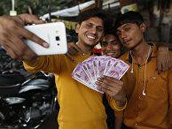 Молодые люди фотографируются с купюрами достоинством в 2000 рупий после денежной реформы в Индии