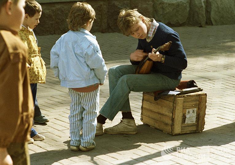 Дети наблюдают за игрой уличного музыканта на Старом Арбате