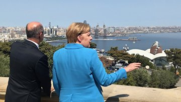 Канцлер Германии Ангела Меркель и министр энергетики Азербайджана Парвиз Шахбазов на фоне панорамы города Баку, Азербайджан. 25 августа 2018