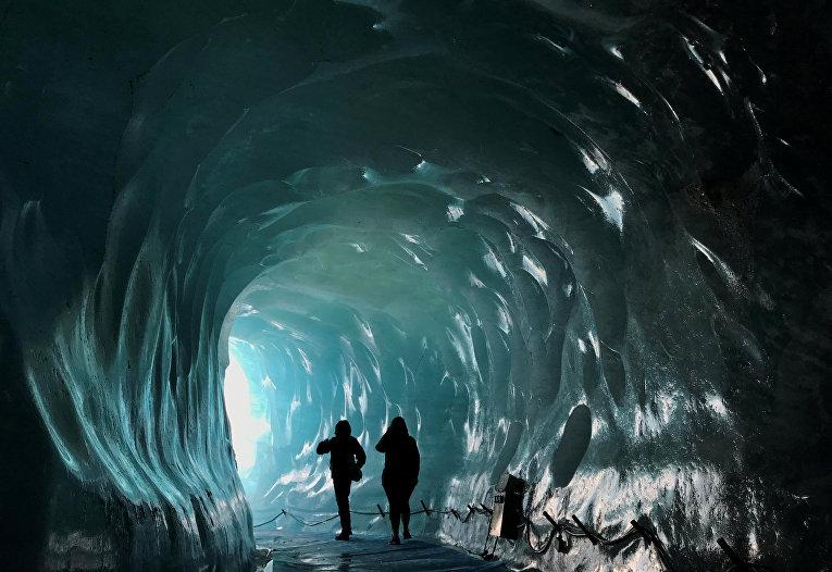 Посетители искусственной ледяной пещеры внутри ледника Мер-де-Глас во французских Альпах