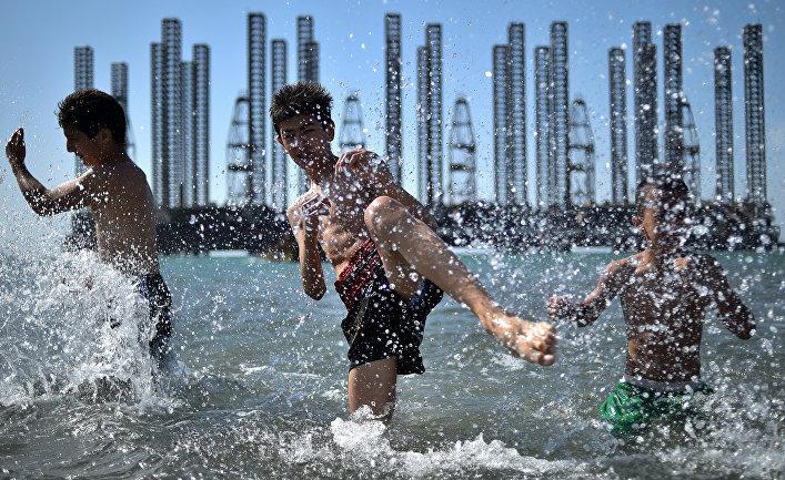 Подростки из школы бокса во время тренировки в Каспийском море у нефтяных вышек в Баку