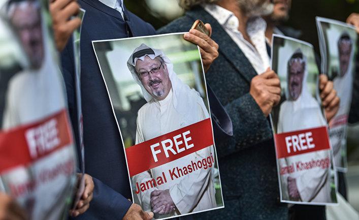 Демонстранты держат фотографии пропавшего журналиста Джамала Хашоги перед консульством Саудовской Аравии в Стамбуле