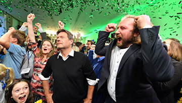Лидер партии Зеленых Роберт Хабек (в центре) и Антон Хофрайтер (справа) празднуют на выборах в государственный парламентев Мюнхене