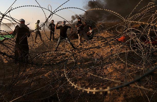 Палестинцы бросают камни в израильские войска во время протеста