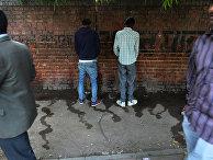 Индийские мужчины используют стенку в качестве туалета в Нью-Дели