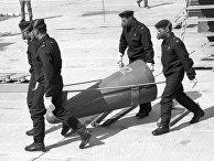 Технические специалисты несут головную часть снятой с боевого дежурства ракеты РСД-10