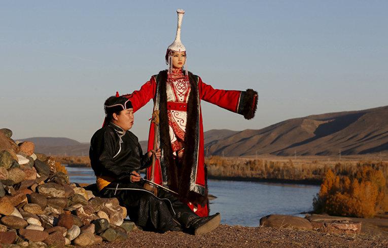Мастер горлового пения Айкхан Оржак и модель Чоргана Кертек выступают на берегу реки Енисей