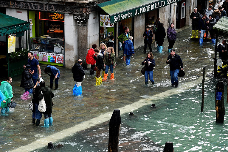 Туристы на затопленной улице возле моста Риальто