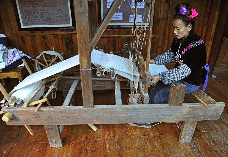 Представительница народности Миао прядет ткань