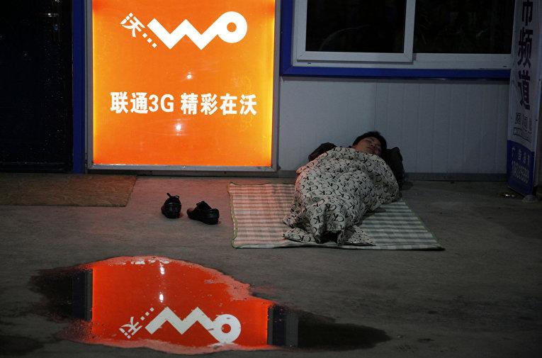 Пассажир спит на вокзале рядом с рекламой Unicom's 3G в городе Шэньян провинции Ляонин, Китай