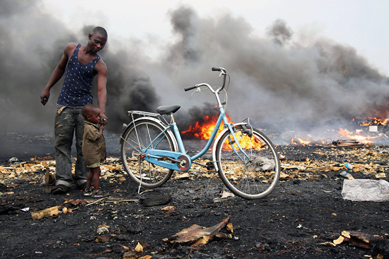 Мужчина с ребенком стоят на фоне дыма в районе Агбогблоши (Agbogbloshie), составляющем агломерацию столицы Ганы