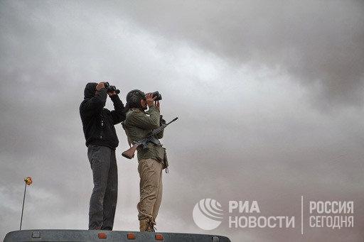 Наблюдатели с биноклями высматривают в небе города Рас Лануф истребители