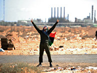 ливийский оппозиционер на фоне нефтяного завода в ливии