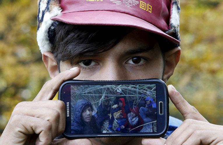 Акрам, беженец из города Герат в Афганистане, показывает фотографию своих друзей