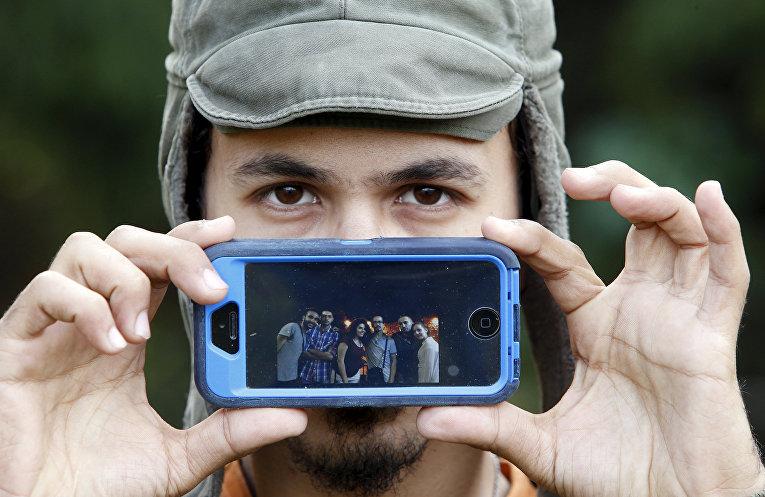 Мухаммад, беженец из Дамаска, показывает фотографию своих лучших друзей