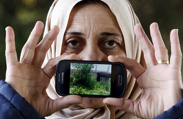 Лоджин, беженка из Хамсло в Сирии, показывает фотографию своего дома