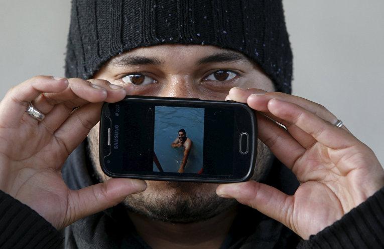 Хаммад, беженец из Дамаска, показывает фотографию, на которой он плавает в бассейне