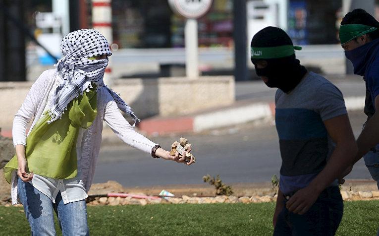 Девушка-палестинка раздает камни протестующим во время столкновений с полицией в городе Бейт-Эль