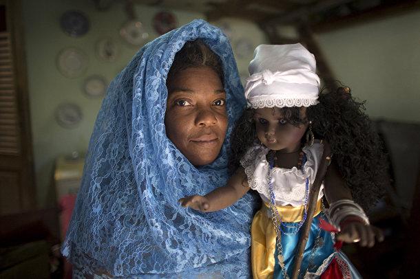 Ньюрка Мола с куклой, символизирующей африканскую морскую богиню Йемайю