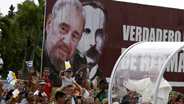 Папамобиль проезжает мимо щита с изображениями Фиделя Кастро и Хосе Марти